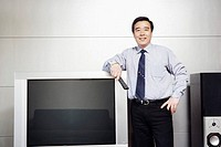 Businessman standing beside a television smiling