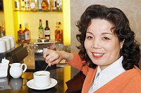 Portrait of a mature woman stirring a cup of coffee