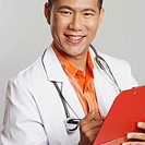 Portrait of a male doctor writing on a clipboard and smiling