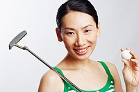 Portrait of a mid adult woman holding a golf club and a golf ball