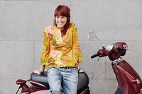 Young woman sitting on a motor scooter and smiling