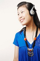 Close-up of a young woman wearing headphones and listening to music