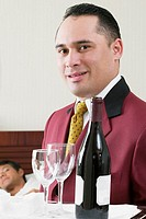 Portrait of a waiter holding a tray with a wine bottle and two wineglasses