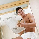 Low angle view of a young man sitting in the bathroom holding a newspaper