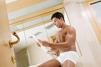 Low angle view of a young man sitting in the bathroom reading a newspaper