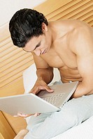 Side profile of a young man sitting on the bed and using a laptop