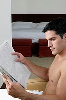 Side profile of a young man reading a newspaper