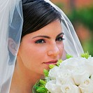 Close-up of a bride smelling a bouquet of flowers