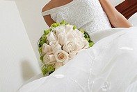 Mid section view of a bride lying on the bed and holding a bouquet of flowers