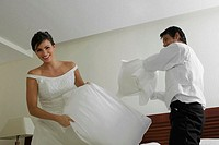 Newlywed couple having a pillow fight on the bed