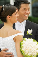 Close-up of a groom embracing his bride and smiling
