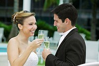 Side profile of a bride and her groom toasting with champagne flutes