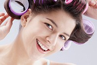 Portrait of a young woman putting curlers in her hair