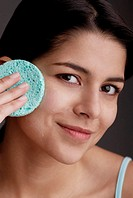 Portrait of a young woman scrubbing her face with a sponge