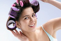 Close-up of a young woman putting curlers in her hair