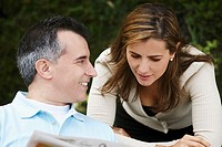 Close-up of a mature man and a mid adult woman reading a newspaper