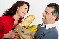 Close-up of a mid adult couple holding a shopping bag and smiling