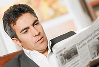 Close-up of a mature man reading a newspaper