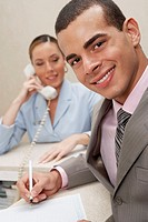 Portrait of a businessman smiling with a female receptionist talking on the telephone behind him
