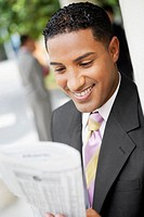 Close-up of a businessman reading a newspaper and smiling