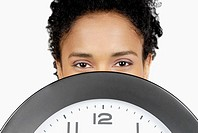 Portrait of a businesswoman hiding her face behind a clock