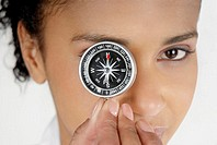 Portrait of a businesswoman covering her eye with a compass