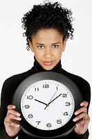 Portrait of a businesswoman holding a clock (thumbnail)