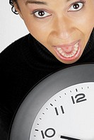 Portrait of a businesswoman holding a clock with her mouth open