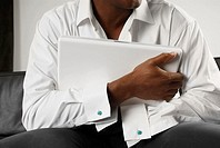 Mid section view of a person hugging a laptop