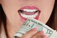 Close-up of a businesswoman holding a bundle of dollar bills near her mouth