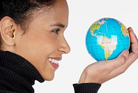 Side profile of a businesswoman holding a globe and smiling