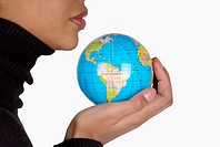 Side profile of a businesswoman holding a globe