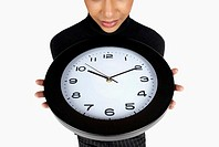 Close-up of a businesswoman holding a clock