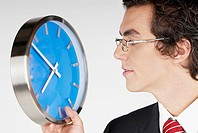 Close-up of a businessman holding a clock