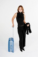 Portrait of a businesswoman standing with a suitcase and smiling