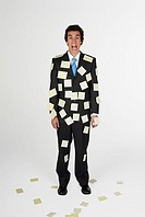 Portrait of a businessman standing with adhesive notes on his body