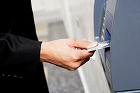 Close-up of a person´s hand inserting a credit card into an ATM