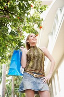 Low angle view of a young woman holding a shopping bag