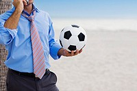 Mid section view of a man holding a soccer ball and talking on a mobile phone (thumbnail)
