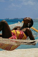 Desiree Lynes wearing a sarong lies on a hammock, Crystal Palace Hotel, Nassau, Bermuda