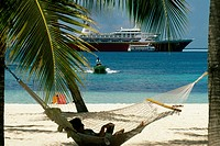 A woman relaxing on a hammock on a beach, Treasure Island, Abaco, Bahamas
