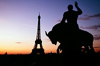 Silhouette of a statue with Eiffel tower and Eid Alliot Palace in the background, France