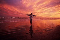Man standing on the beach with his arms outstretched, Texas, USA