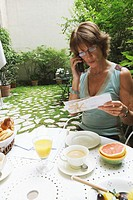 Mature woman holding letter using mobile phone at breakfast in garden