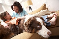 Mother with daughter (8-10) relaxing on sofa with dog