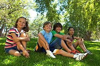 Group of children (9-12) in park, sitting on grass, smiling