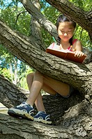 Girl (9-11) sitting in branches of tree writing in book,low angle view