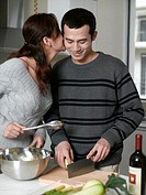 Young woman whispering to man preparing vegetables in kitchen