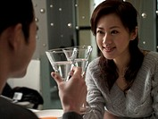 Young couple at dinner table, raising glasses together, close-up