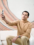 Young man relaxing on sofa, holding up mobile phone to take photograph